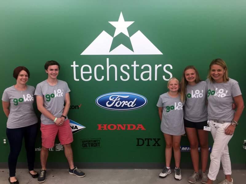 GoKid team + Founder's children standing in front of the Techstars logo at Techstars Mobility Detroit